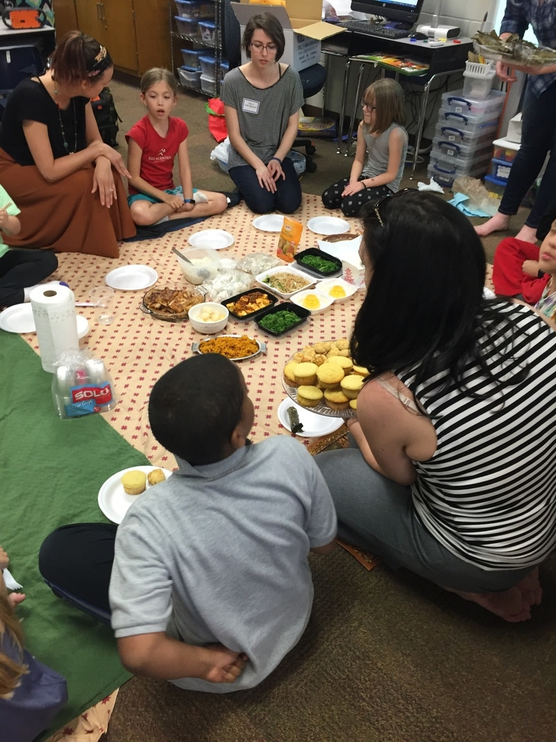 Students sitting around a picnic blanket with Southeast Asian cuisine. These students are participating in a traditional Southeast Asian feast